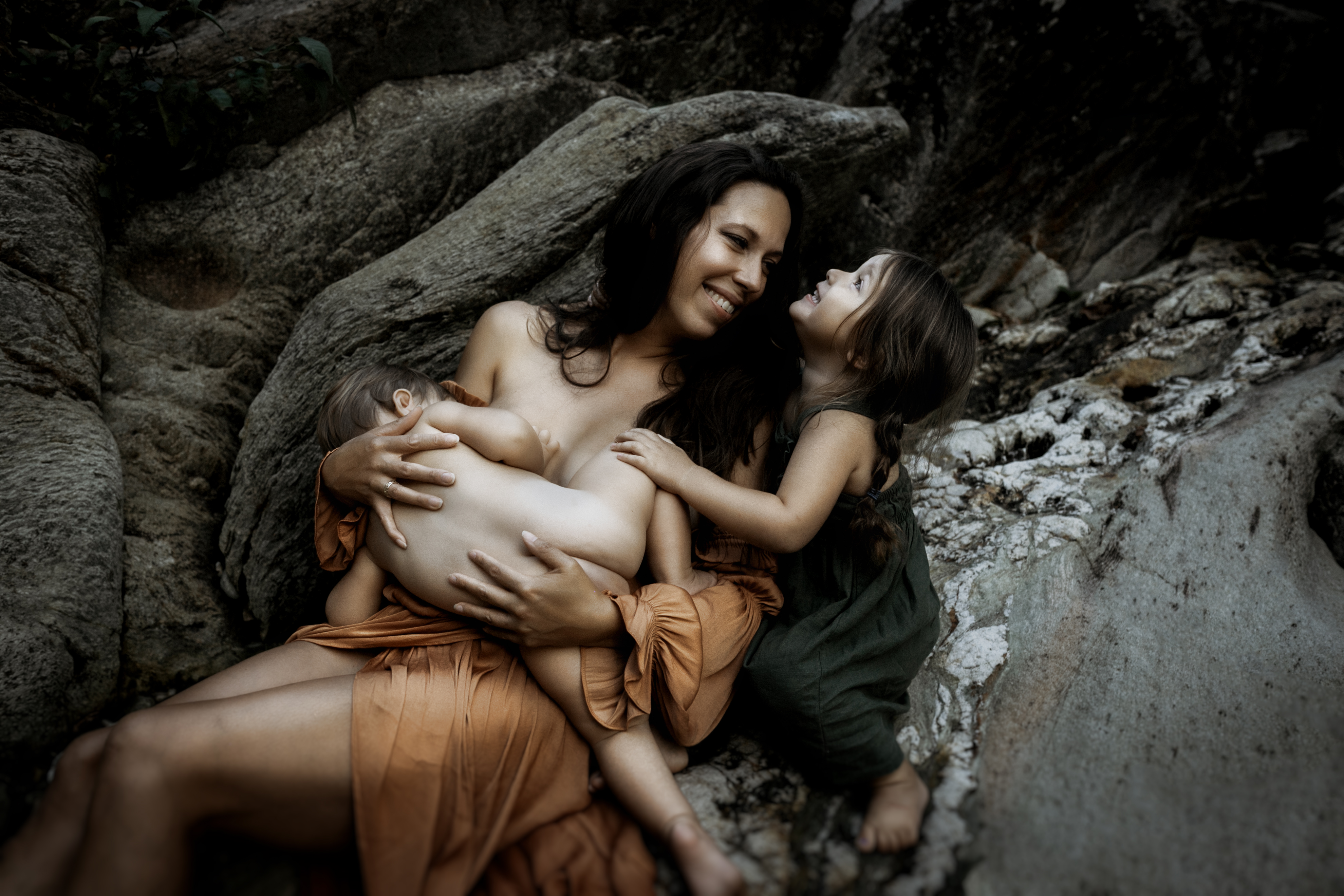 """""""Colorful photograph of mother holding breast feeding daughter by Megan Marie Photographer."""""""