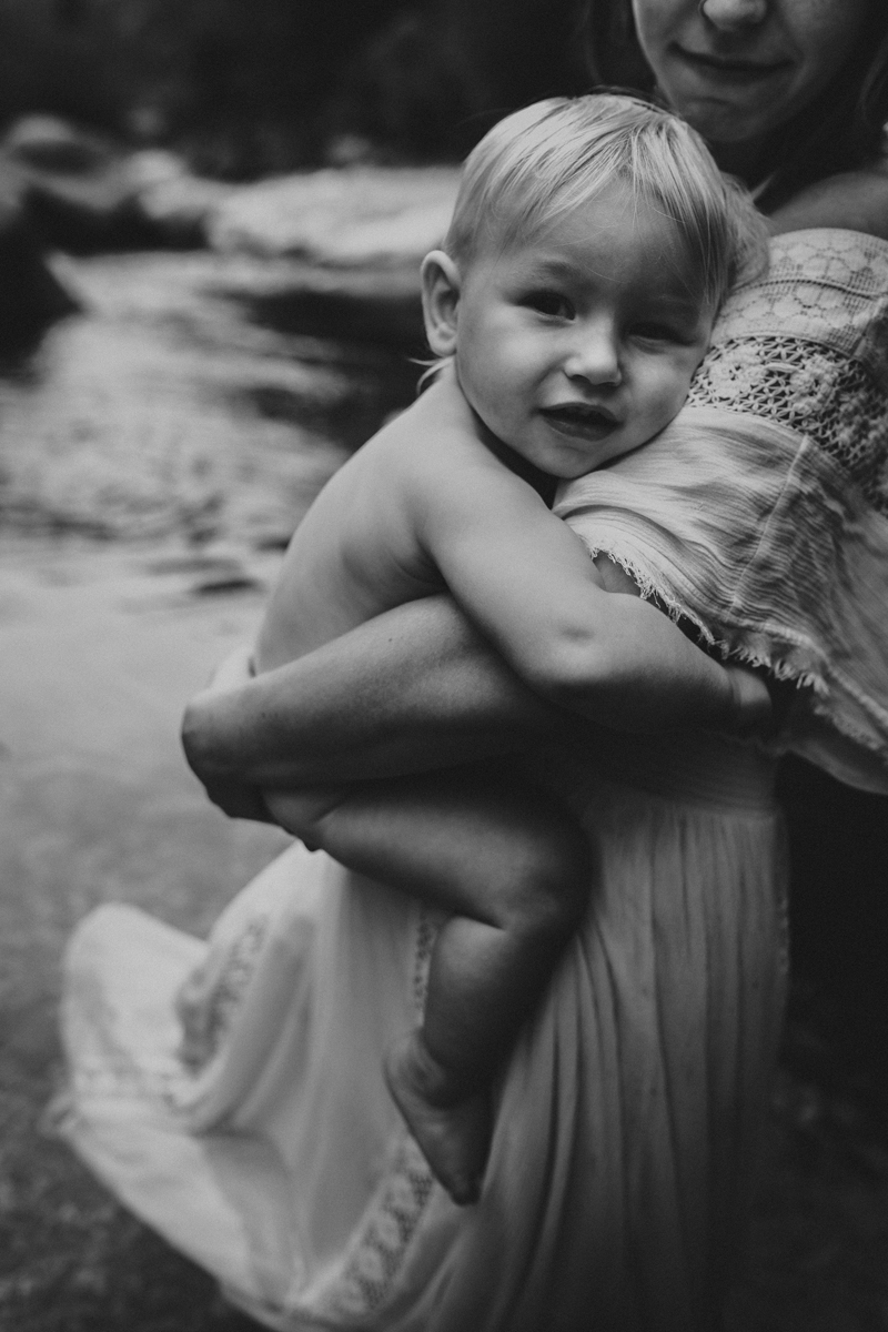 """""""Black and white photograph of mother holding her child in river by Megan Marie Photographer."""""""