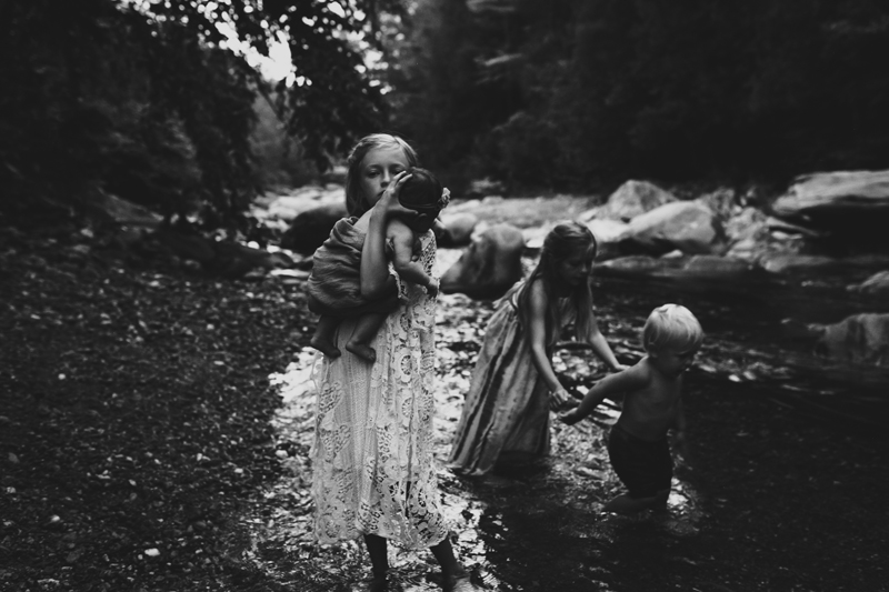 """""""Black and white photograph of older sister holding baby sister along river by Megan Marie Photographer."""""""